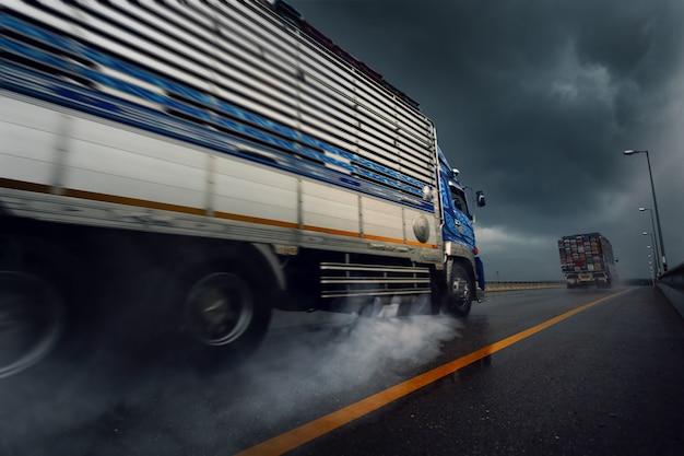 Vrachtwagen rijdt snel op natte weg na zware regenval, slechte weersomstandigheden.