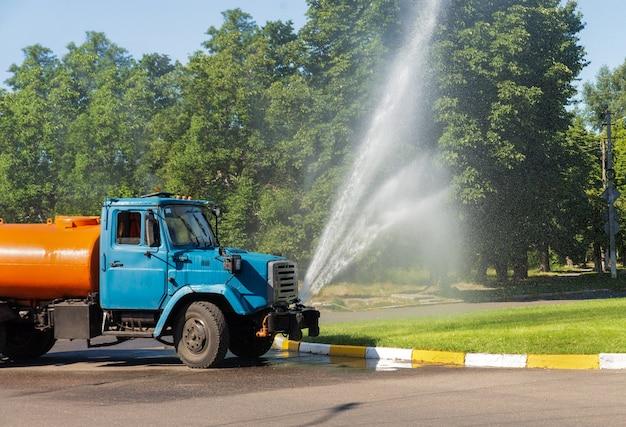 Vrachtwagen sprenkelt water op een groen gazon in de stad. stedelijke economie. verbetering van groene zones.