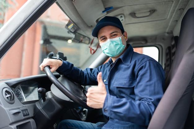 Vrachtwagenchauffeur die duimen opgeeft tijdens pandemie van het coronavirus