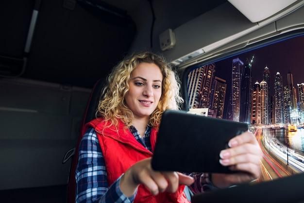 Vrachtwagenchauffeur die een gps-navigatiesysteem gebruikt om door groot stadsverkeer te navigeren om naar de bestemming te gaan