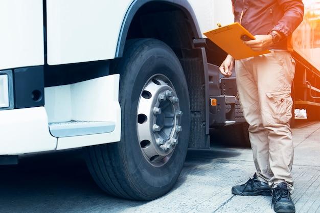 Vrachtwagenchauffeur die klembord met cheking veiligheid van bandenvrachtwagen.