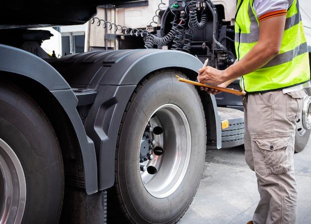 Vrachtwagenchauffeur hand houden klembord met inspectie van een vrachtwagen banden.