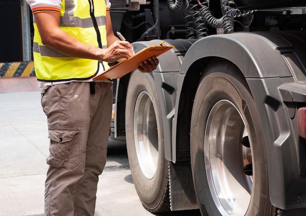 Vrachtwagenchauffeur hand houden klembord met inspectie van een vrachtwagen wielen.