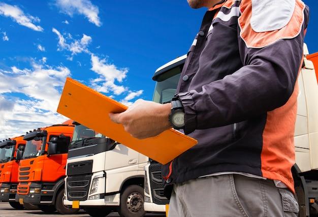 Vrachtwagenchauffeur houden een klembord met het inspecteren van vrachtwagens.