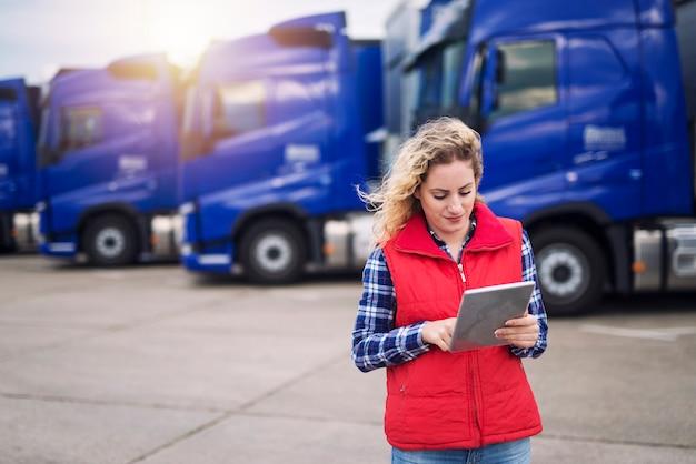 Vrachtwagenchauffeur houdt tablet en controleert route voor nieuwe bestemming.