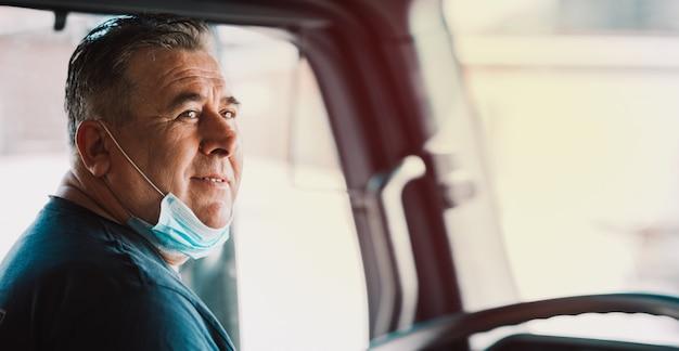 Vrachtwagenchauffeur in de cabine met een medisch masker op zijn gezicht