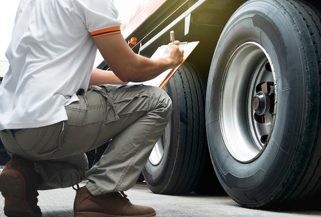 Vrachtwagenchauffeur inspecteert de veiligheid van wielen vrachtwagen.