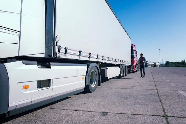 Vrachtwagenchauffeur inspecteert vrachtwagen lang voertuig voordat hij gaat rijden