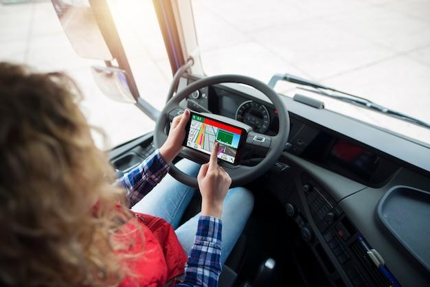 Vrachtwagenchauffeur met behulp van gps-navigatie voor wereldwijde positionering voor de bestemming.