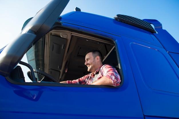 Vrachtwagenchauffeur zit in zijn cabine zijn vrachtwagen besturen.