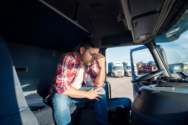 Vrachtwagenchauffeur zit in zijn vrachtwagencabine bezorgd en boos