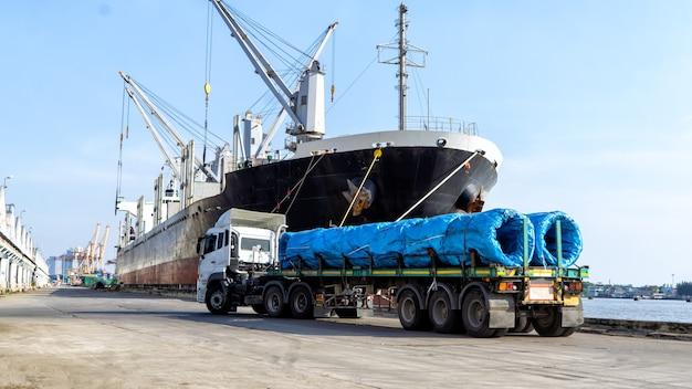 Vrachtwagencontainer tegen schip met kraan bij haven.