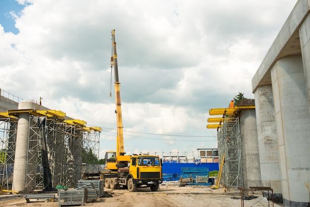 Vrachtwagenkraan op een bouwplaats tijdens de bouw van een transportbrug