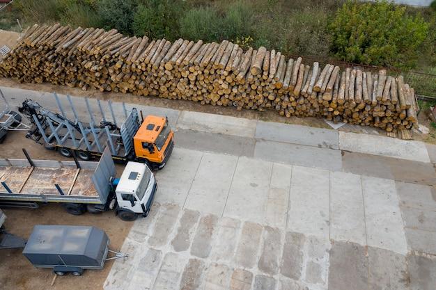 Vrachtwagens bij een stapel houtblokken wachten om geladen te worden.