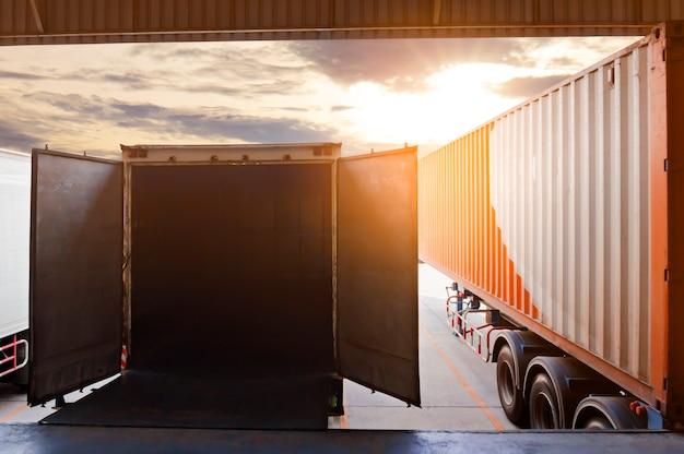 Vrachtwagens die bij open deuren in het magazijn aanmeren, logistiek in de vrachtindustrie en transport
