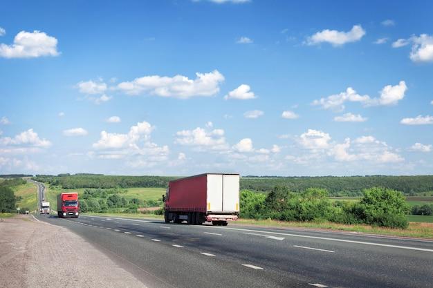 Vrachtwagens en auto's rijden langs de zomerweg, de snelweg.