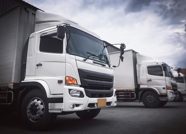 Vrachtwagens geparkeerd laden bij dok magazijn levering vracht zending vracht vrachtwagen transport logistiek