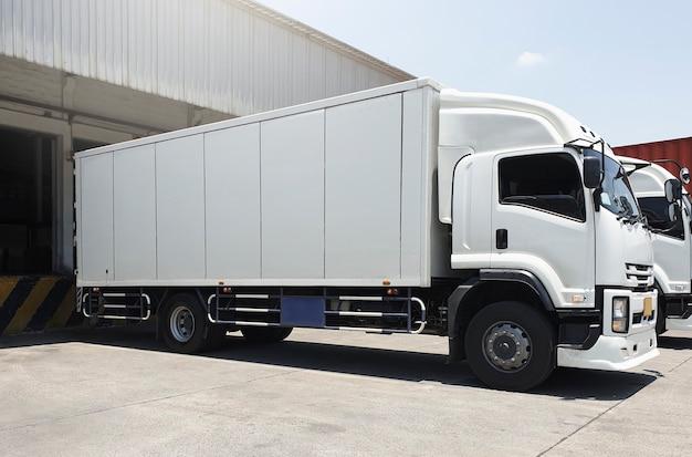 Vrachtwagens geparkeerd laden bij dok magazijn vracht vrachtwagen transport verzending magazijn logistiek