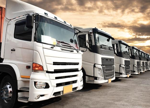 Vrachtwagens geparkeerd opgesteld bij zonsonderganghemel, logistiek van de wegvrachtindustrie en transport