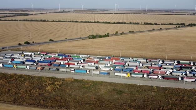 Vrachtwagens met aanhangers staan in een lange rij bij de haventerminal voor het lossen van graan.
