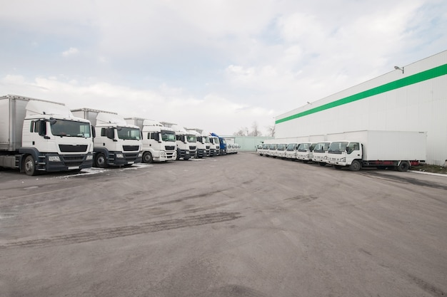 Vrachtwagens staan in een rij op een parkeerplaats in de buurt van het fabrieksmagazijn vrachtwagen in het magazijn