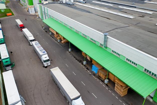 Vrachtwagens wachten om geladen te worden in de fabriek, bovenaanzicht.