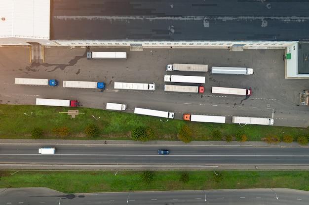 Vrachtwagens wachten om te worden geladen in het bovenaanzicht van het logistiek centrum.
