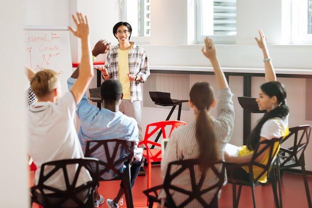 Vragen hebben. actieve jonge mensen die geïnteresseerd zijn in zelfgroei die naar de spreker kijken en hun hand opsteken terwijl ze vragen hebben