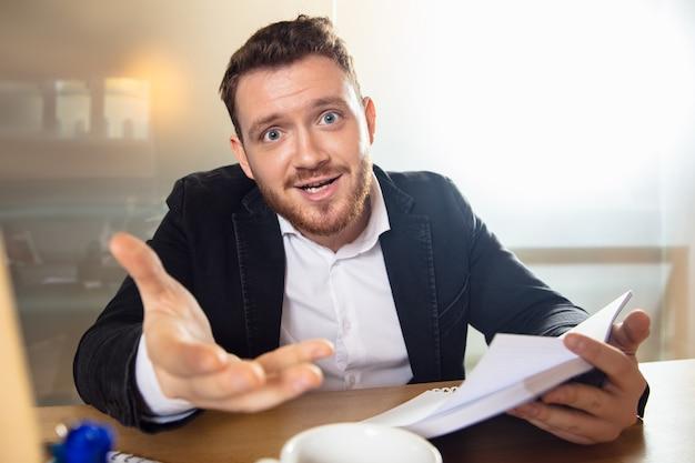 Vragen. jonge man aan het werk in videoconferentie met collega's op kantoor. online zakendoen, onderwijs tijdens coronavirus en quarantaine. werk, financiën, modern tech concept. uitzicht vanaf het scherm.