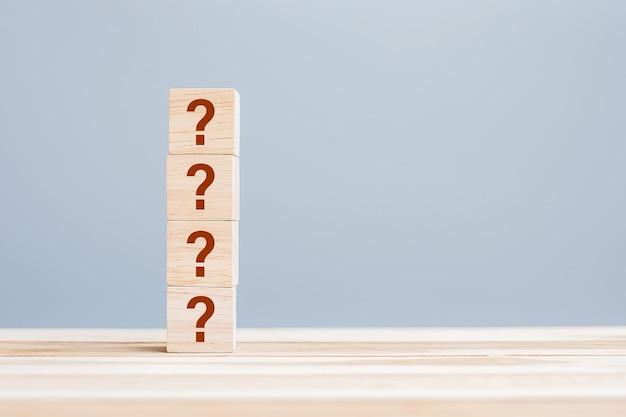 Vragen markeer (?) op houten kubusblok op tafelachtergrond. veelgestelde vragen (frequentie gestelde vragen), antwoord, vragen en antwoorden, informatie, communicatie en ondervragingsconcepten