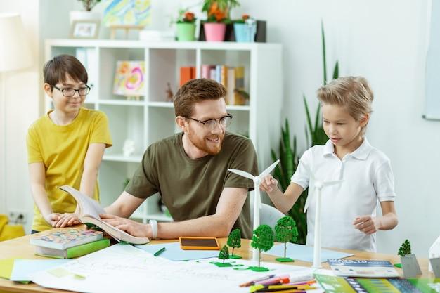 Vragen over ecologie. attente blonde jongen die geïnteresseerd is in plastic modellen van windmolens terwijl ze ecologie bespreken