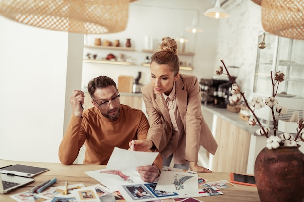 Vragen voor hulp. mooie geconcentreerde assistent die modeontwerper helpt met zijn nieuwe schetsen die naar een van hen wijzen.