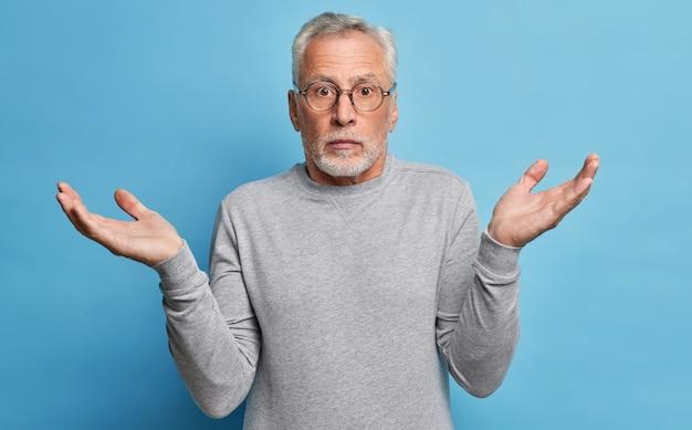 Vragende verbaasde grijsharige man spreidt handen in geen idee, haalt zijn schouders op, moet een keuze maken gekleed in vrijetijdskleding kan niet begrijpen wat er mis is met blikken met een verbijsterde uitdrukking