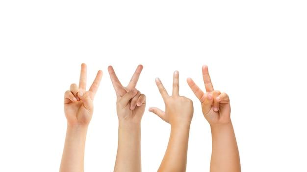 Vrede, groet. kinderen handen gebaren geïsoleerd op een witte studio achtergrond, copyspace voor advertentie. menigte van kinderen gebaren. concept van kindertijd, onderwijs, voorschoolse en schooltijd. tekenen en zintuigen.