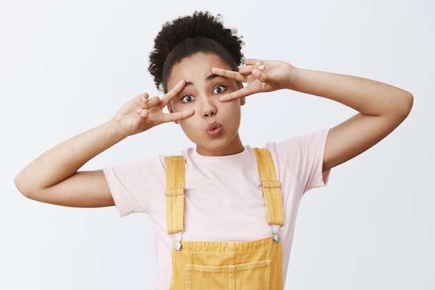 Vrede in ons hart. trendy goed uitziend modern afrikaans amerikaans meisje in gele overall over t-shirt, hoofd kantelend, lippen vouwen in kus en overwinningstekens boven ogen tonen vreugdevol, in disco-stemming