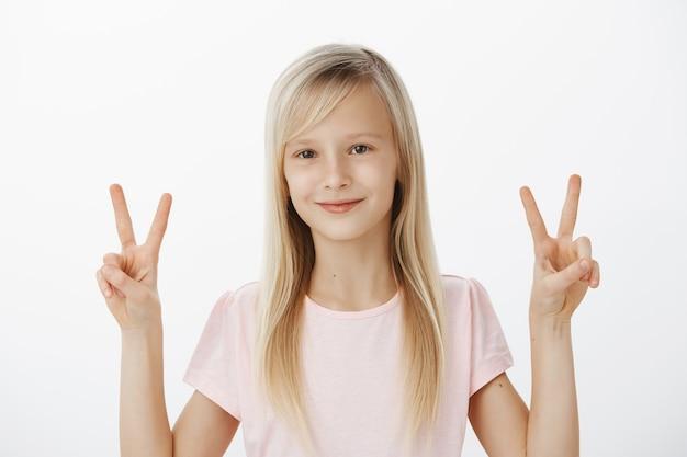 Vrede kinderen. emotioneel vrolijk jong meisje met een positieve instelling, vriendelijk lachend en met beide handen overwinning of v-borden, foto's maken voor kinderwedstrijd over grijze muur