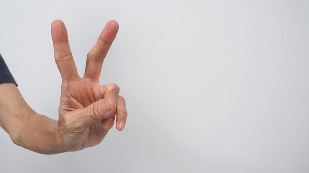 Vrede of good luck handteken doen door senior of oudere vrouw. het is voor handgebaren met twee vingers op een witte achtergrond