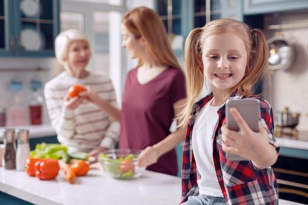 Vrede thuis. aangename jonge vrouw zittend op het aanrecht en selfies nemen van zichzelf en haar moeder en grootmoeder salade koken