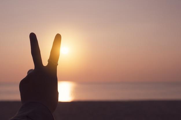 Vrede uit of vechten metafoor twee vingers handteken voor een zonsondergang.