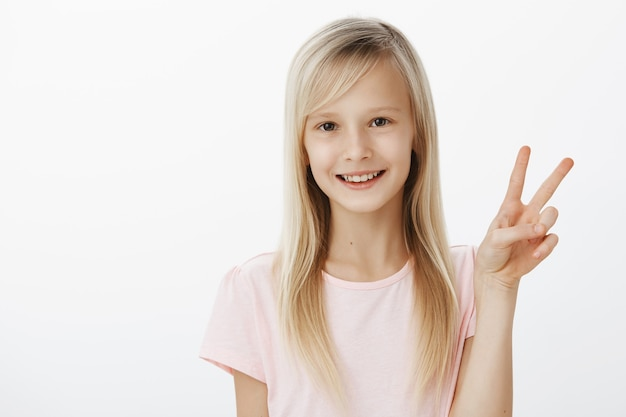 Vrede voor al mijn fans. portret van schattig modieus klein europees meisje in roze t-shirt die overwinningsgebaar tonen en breed glimlachen, zich zorgeloos en zelfverzekerd voelen over grijze muur