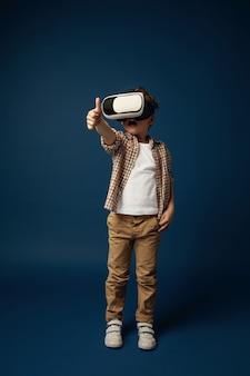 Vrede voor andere planeten. kleine jongen of kind in jeans en shirt met virtual reality headset bril geïsoleerd op blauwe studio achtergrond. concept van geavanceerde technologie, videogames, innovatie.