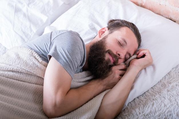 Vreedzaam en gezond slapen. comfortabele zachtheid van warm bed. man slapen met gelukkige gezichtsuitdrukking. rust en gezelligheid.