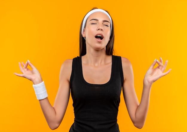 Vreedzaam jong vrij sportief meisje die hoofdband en polsband dragen die met gesloten ogen en open mond mediteren die op oranje ruimte wordt geïsoleerd