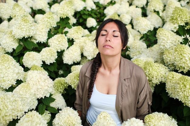 Vreedzaam volwassen vrouwtje in een veld met witte hortensia's die met haar ogen dicht staan.
