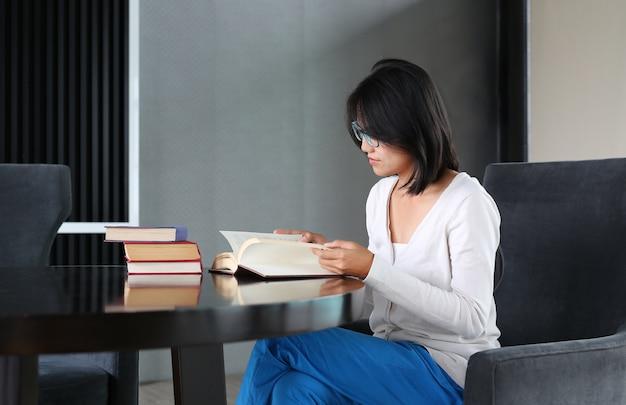 Vreedzame aziatische vrouw die een boek in de bibliotheek leest