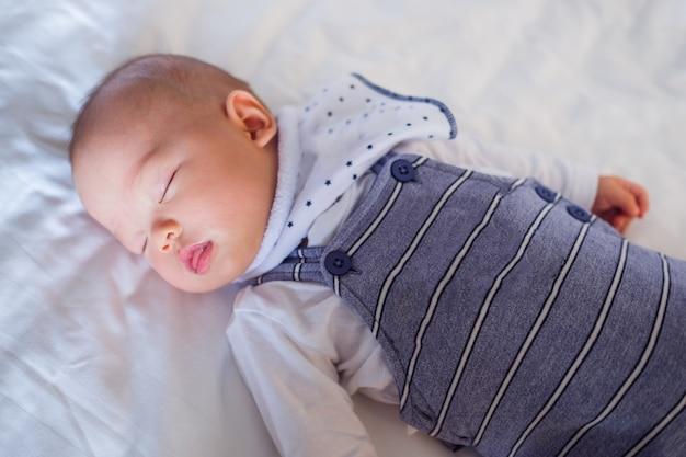 Vreedzame baby liggend op een bed tijdens het slapen in een lichte kamer