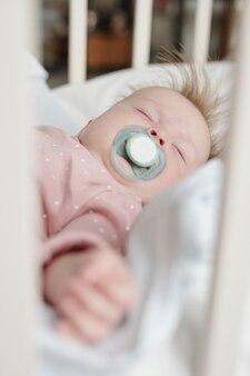 Vreedzame baby met fopspeen in de mond die midden op de dag rust