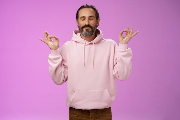 Vreedzame charmante hipster oude man draagt cool roze hoodie sluit ogen ademhaling praktijk vrijlating stress mediteren staande ontspannen gelukkig yoga meditatie pose nirvana gebaar, paarse achtergrond.