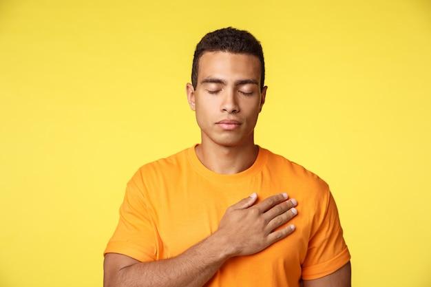 Vreedzame en hoopvolle jonge knappe man legt hand op hart