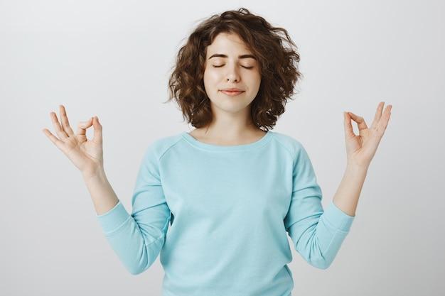 Vreedzame en ontspannen glimlachende vrouw die met gesloten ogen mediteert om nirvana te vinden